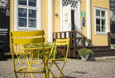 Gula cafémöbler utanför Silvermuseets huvudentré. Soligt, några buskar och krukor med blommor syns i bakgrunden.
